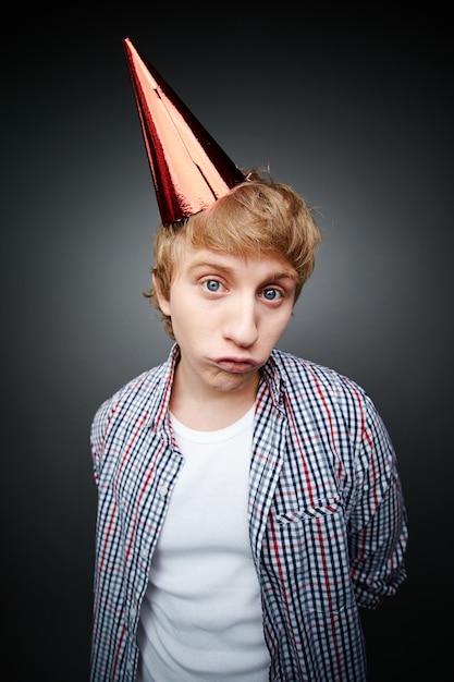 Sad boy with red birthday hat Free Photo