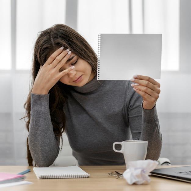 Donna di affari triste che tiene un blocco note in bianco Foto Gratuite