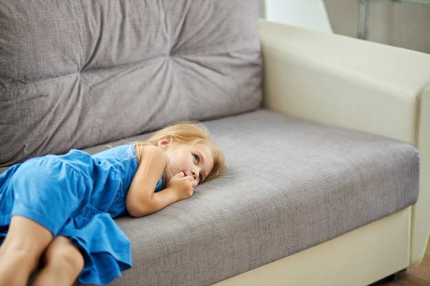 Грустная кавказская маленькая девочка, лежащая на диване в одиночестве, расстроена, глядя в сторону Premium Фотографии