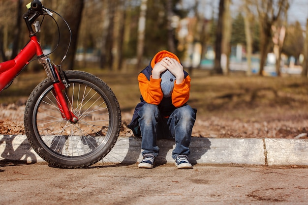 Sad child sitting near a broken bicycle Premium Photo