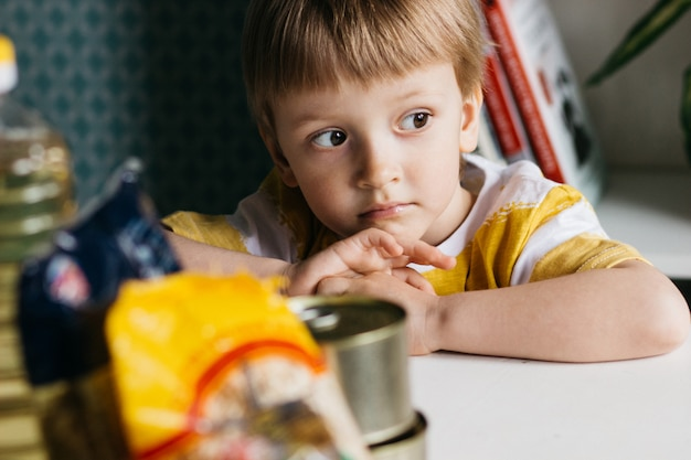 Sad child with donated food. food delivery concept. Premium Photo