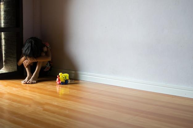Sad children,girl sitting alone in corner at home Premium Photo