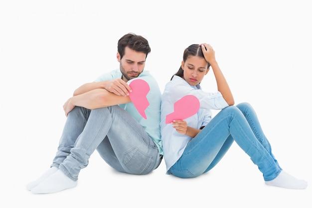 Sad couple sitting holding two halves of broken heart Premium Photo