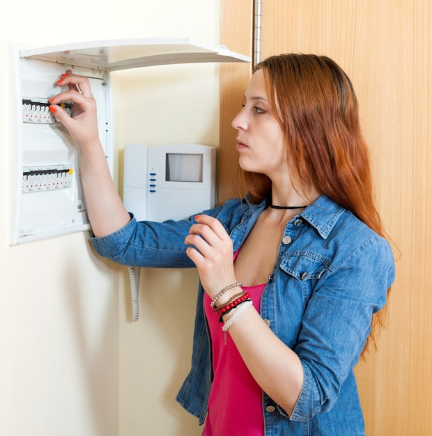 Sad cute woman near power control panel Free Photo