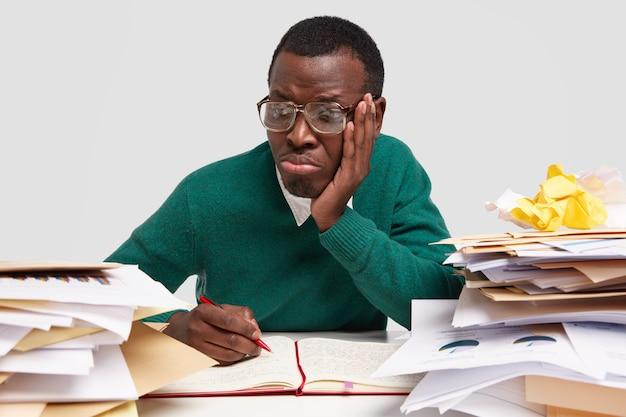 悲しい暗い肌の男性のヒップスターは、過労、過負荷を感じ、ノートにアイデアを書き留め、不快な唇を財布に入れ、視力を良くするために大きな四角い眼鏡をかけます 無料写真