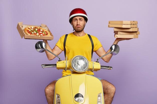 ピザの箱を持って黄色いスクーターを運転する悲しい配達員 無料写真