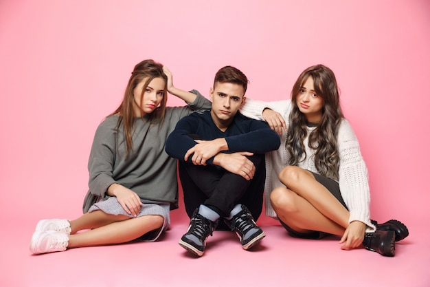 Sad displeased young friends sitting on pink floor Free Photo