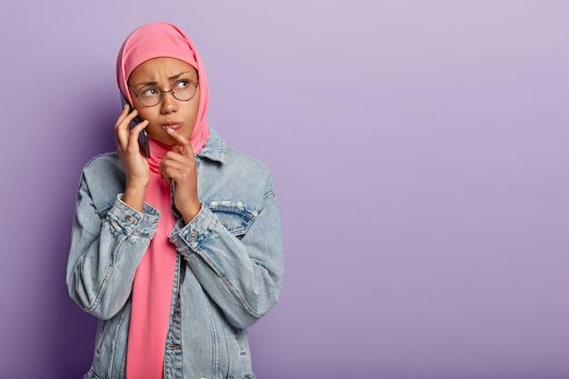 Грустная недовольная темнокожая женщина в розовом хиджабе в джинсовой куртке и круглых очках Бесплатные Фотографии