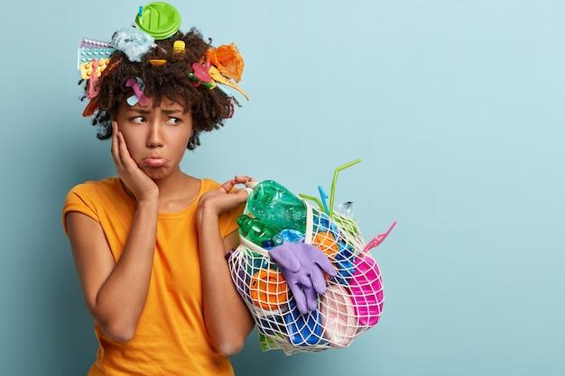 Triste donne insoddisfatte porta il labbro inferiore, guarda con rabbia da parte, tiene una borsa a rete con rifiuti di plastica, pulisce il territorio, è eco-amichevole, arrabbiata con le persone che inquinano l'ambiente, indossa una maglietta arancione Foto Gratuite