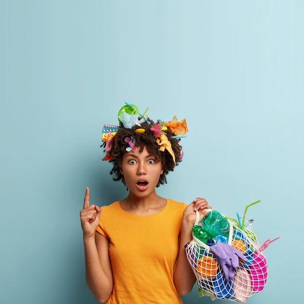 Una donna triste e insoddisfatta porta il labbro inferiore, guarda con rabbia da parte, tiene in mano una borsa a rete con rifiuti di plastica, pulisce il territorio Foto Gratuite
