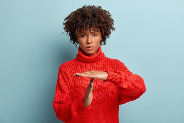 Грустная недовольная уставшая разочарованная женщина показывает жест тайм-аута, нуждается в остановке, просит время для отдыха после тяжелой работы, демонстрирует знак сломанной руки, носит красный джемпер. концепция языка тела Бесплатные Фотографии