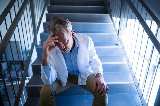 階段に座っている悲しい医師 無料写真