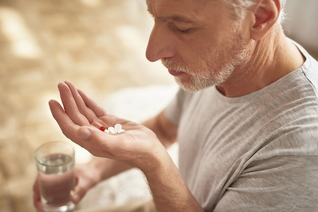 Sad elderly man holding pills and glass of water. Premium Photo