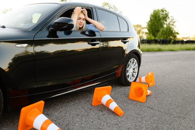 Sad female student in car, all traffic cones are downed, lesson in driving school. Premium Photo