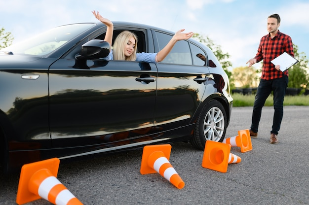 Sad female student in car and instructor, all traffic cones are downed, lesson in driving school. Premium Photo