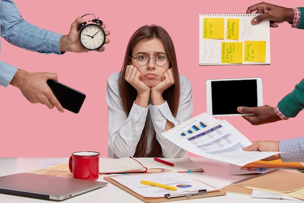 Sad female workaholic keeps hands under chin, busy making project work, studies papers, wears elegant white shirt, sits at desktop, unknown people stretch hands with notes, alarm clock, smartphone Free Photo