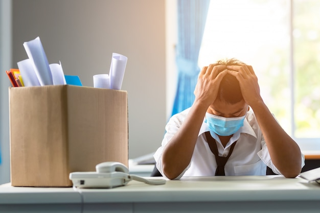 Sad fired asian businessman sitting outside room after being dismissed concept of business failure and unemployment problem due to the global impact of covid-19. Premium Photo