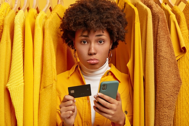 悲しい欲求不満のアフロの女性は、オンラインウォレットを介して支払いを行い、クレジットカードと現代の携帯電話を保持しています 無料写真