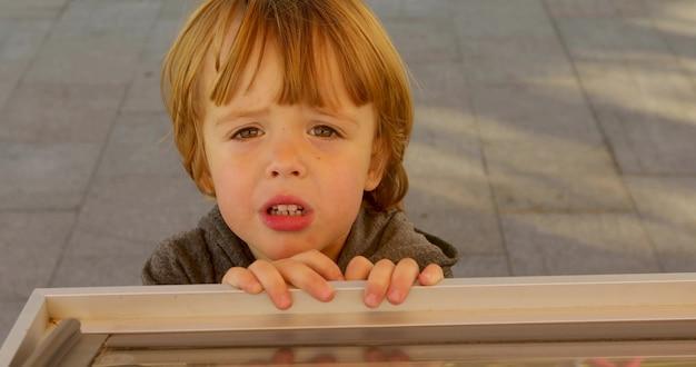 Sad ginger haired boy looking at camera Premium Photo