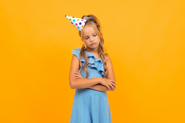 Sad girl in a festive cap crossed her arms on a yellow Premium Photo