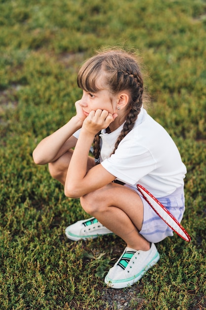 Sad girl with badminton crouching on green grass Free Photo