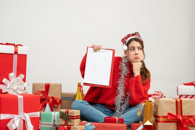 산타 모자 주위에 앉아 파일을 들고 슬픈 소녀 흰색 선물 무료 사진
