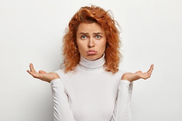 Грустная хмурая рыжая женщина поджимает нижнюю губу, принимает серьезное решение, испытывает сомнение и неуверенность, разводит ладони в стороны, одетая в повседневный белый джемпер, не зная, как решить свою проблему Бесплатные Фотографии