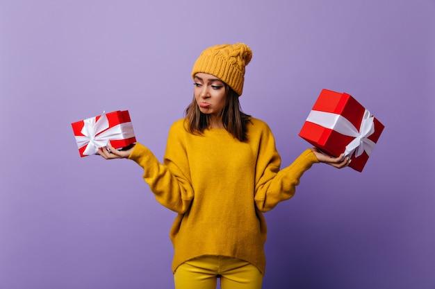 생일 선물을 들고 노란 모자에 슬픈 화려한 소녀. 새 해 파티 후 포즈를 취하는 감정적 인 갈색 머리 아가씨의 실내 초상화. 무료 사진