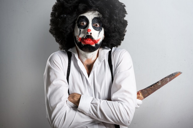 Sad killer clown with knife on textured background Premium Photo