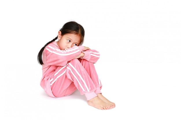 Sad little asian child girl in pink tracksuit or sport cloth sitting and hugging knees Premium Photo