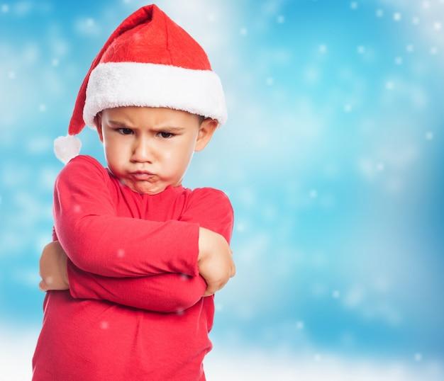 fb5fcdc1e1269 Sad little boy wearing santa hat Free Photo