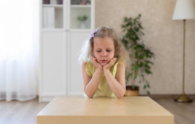 Грустная маленькая девочка сидит за столом и смотрит вниз Premium Фотографии