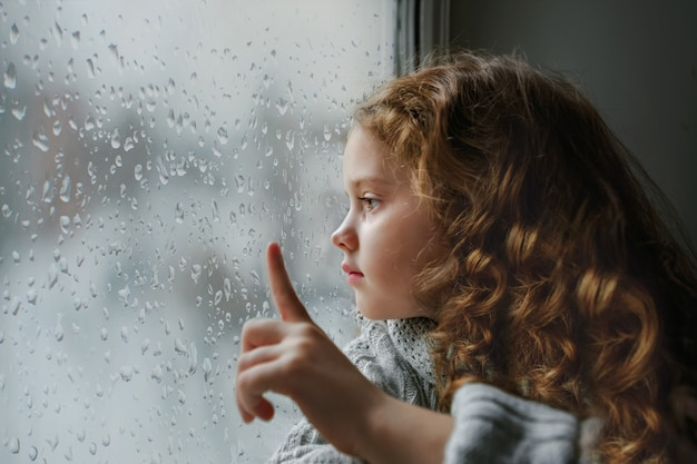 Sad little girl looking out the window on rain drops near wet glass autumn bad weather. Premium Photo