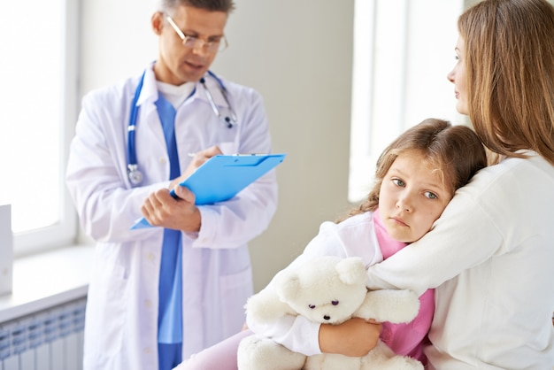 Sad little girl in the medical office Free Photo