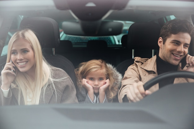 Sad little girl sitting in car while her parents talking Free Photo