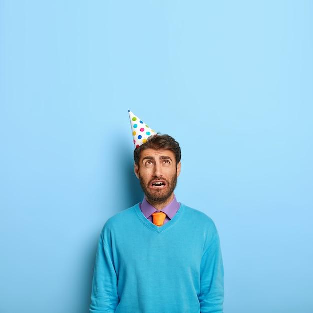 悲しい孤独な誕生日の男はコーン紙の帽子をかぶっています 無料写真