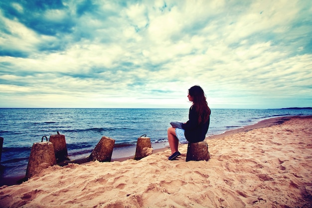 Sad, lonely woman sitting on the beach. Free Photo
