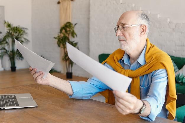 공식적인 옷을 입고 일반 노트북과 함께 나무 책상에 앉아 안경을 쓰고 그의 손에 문서를 들고 좌절하고있는 60 년대의 슬픈 남성 엔지니어. 직업, 직업 및 스트레스 개념 무료 사진