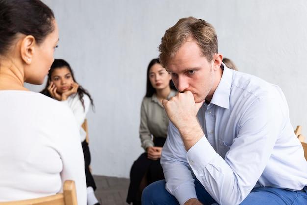 集団療法セッションでの悲しい男 無料写真