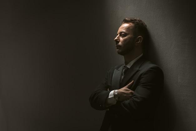 Sad man in black suit on black wall Premium Photo