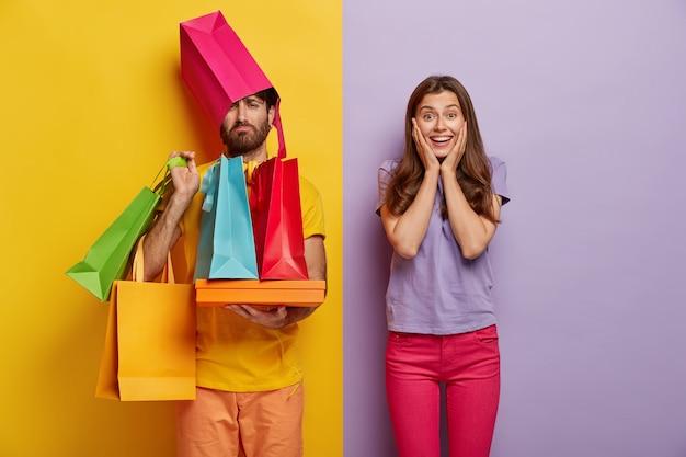 Грустный мужчина перегружен сумками, имеет жену-шопоголку, свободное время в выходные проводит за покупкой новой одежды Бесплатные Фотографии