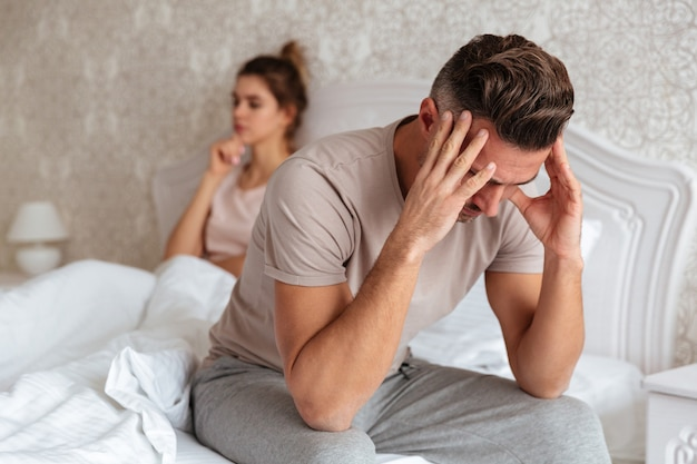 Sad man sitting on bed with his girlfriend Free Photo