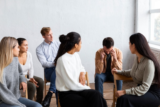 Sad man talking about his issues at a group therapy session Free Photo