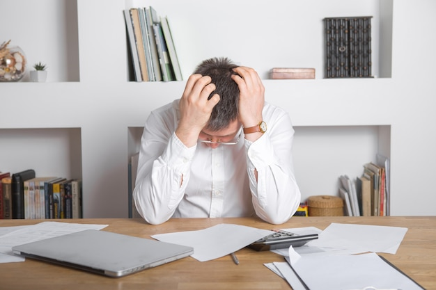 Sad manager getting notice of dismissal, sitting at workplace with laptop and financial documents, employee receiving letter with bad news, entrepreneur upset by commercial failure or firm bankruptcy Premium Photo