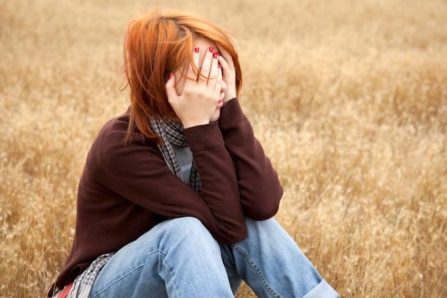 Sad redhead girl sitting on yellow grass at countryside Premium Photo
