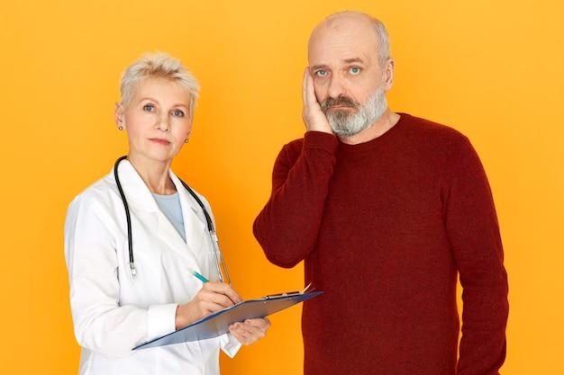クリップボードを保持している白い医療コートで彼女の高齢患者に診断と治療について話している悲しい引退した女性開業医 無料写真