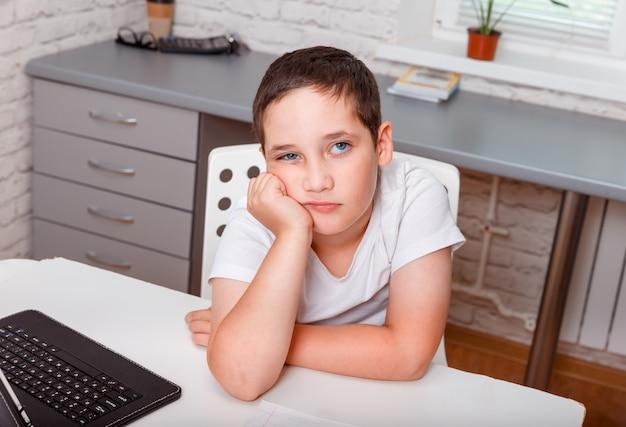 自宅の机に一人で座っている悲しい少年。白いtシャツのしかめっ面の不機嫌そうな小さな男の子、学校での不当な成績に不満 Premium写真
