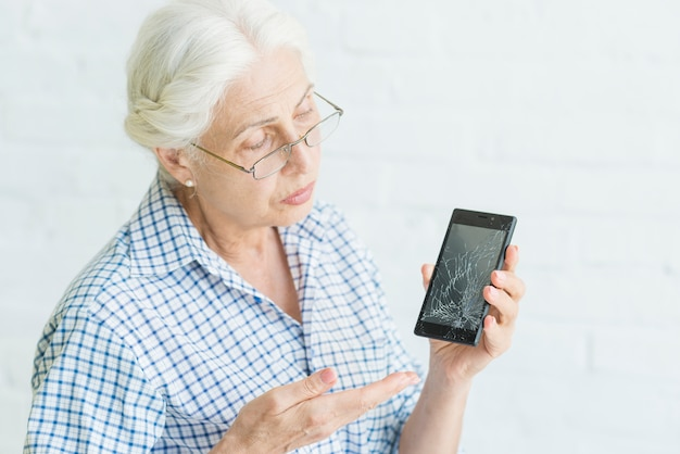 Sad senior woman showing smartphone with broken screen against white backdrop Free Photo