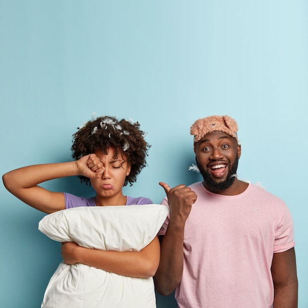 Sad sleepy dark skinned female rubs eyes, wake up early, holds white pillow, wants to sleep more, glad husband wears sleepmask on forehead, points with thumb at tired wife. bad rest concept. Free Photo