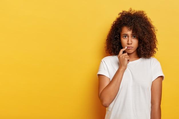 슬픈 찡그린 아프리카 계 미국인 밀레 니얼 여성, 집게 손가락을 입술 근처에두고, 누군가에게 모욕을 당하고, 실망하고, 캐주얼 한 옷을 입고, 노란색 벽에 포즈를 취하고, 문제가 있음 무료 사진